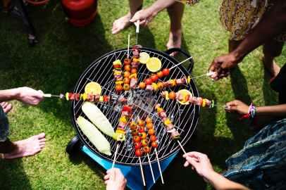 people barbecuing skewered meats