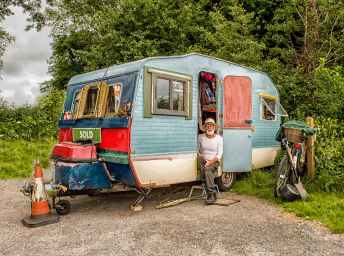 photo of a man in white long sleeved top on blue and white pop up camper
